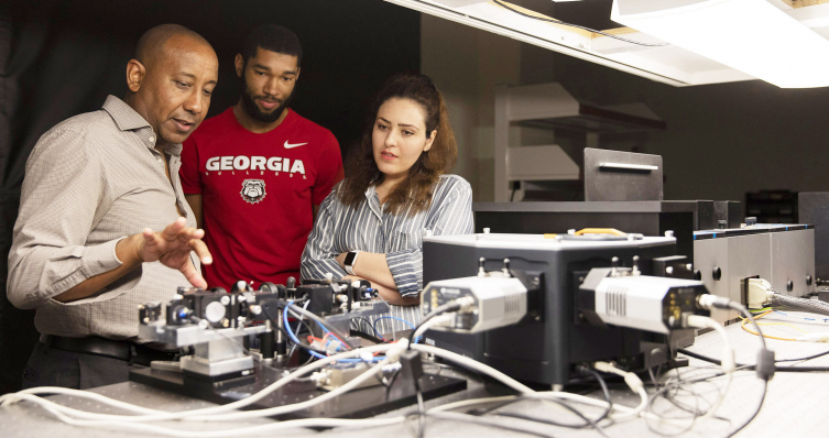 From left, professor Yohannes Abate talks with graduate students Marquez Howard and Neda Aghamiri about equipment used for nanoscale imaging and spectroscopy in his lab.